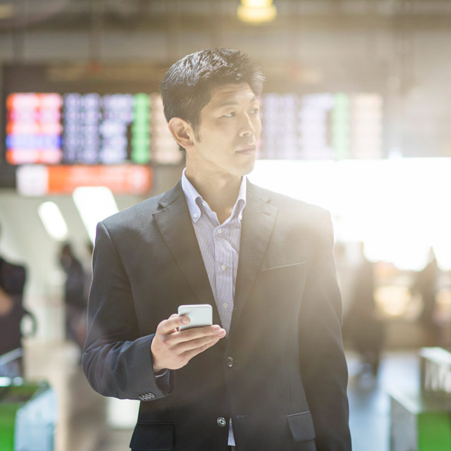 Man at the airport searching on mobile app
